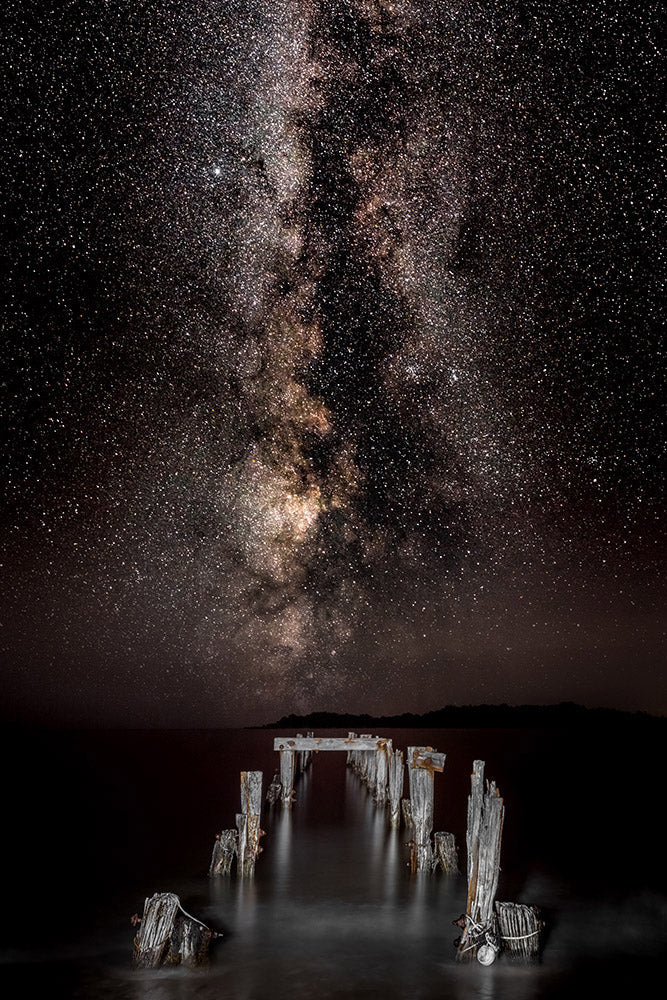 Landscape wall art photography of the Milky Way galaxy rising over decaying pilings at West Beach in Beverly