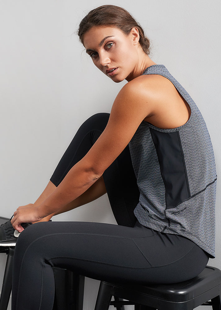 young woman wearing an active wear grey and black tank top side view