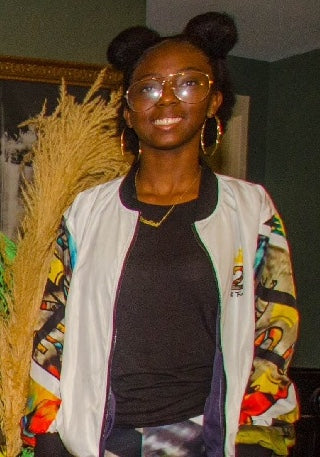 14 y/o Black girl smiling with afro puff hair, wearing gold hoops, necklace and round rim glasses while wearing a jacket and pants from her TwoAndFro.co store. She is the owner of TwoAndFro.co