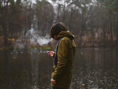 A man in a hoodie smoking in front of a lake