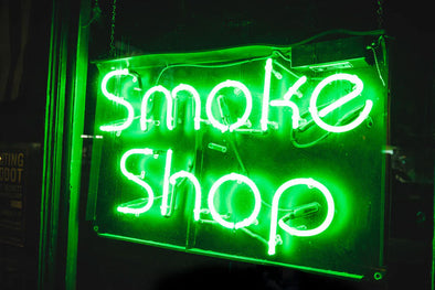 A neon green 'Smoke Shop' sign