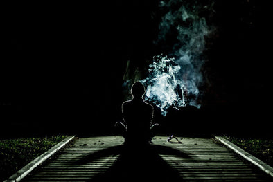 Dark silhouette of man smoking outdoors at night