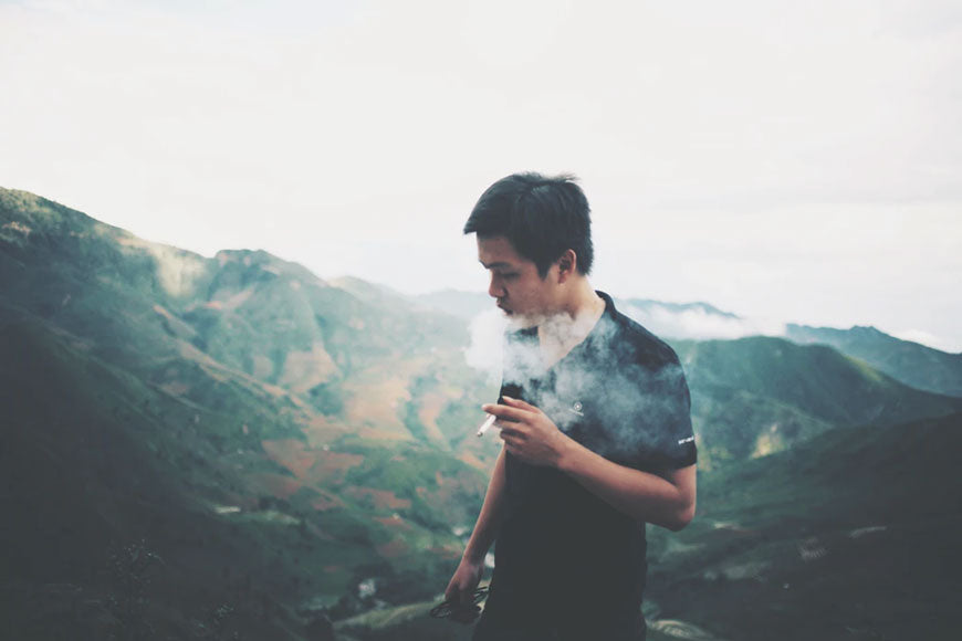 A man smoking while on a hike