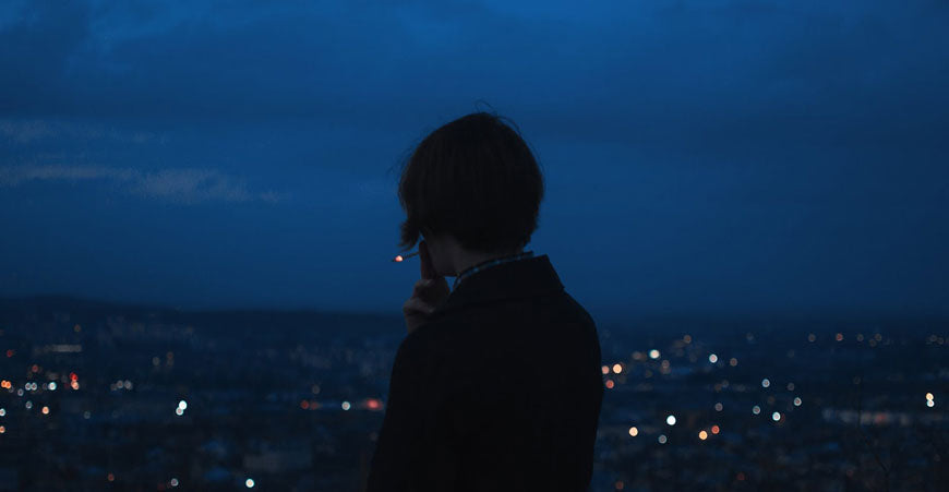 Rear view of man smoking 2 hitter pipe while overlooking a city at night