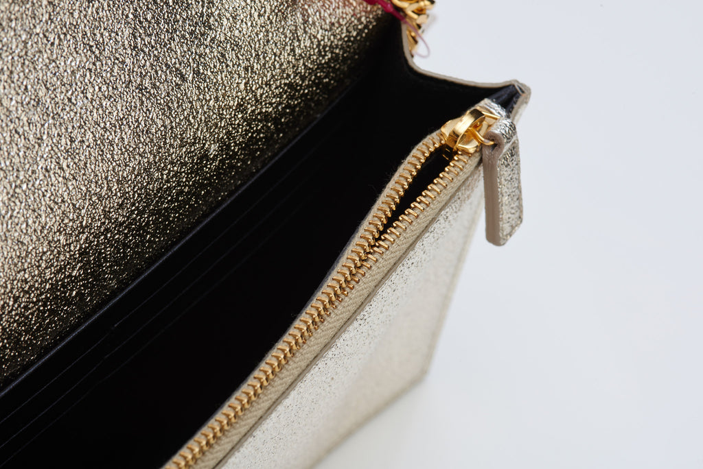 Saint Laurent silver clutch bag with gold shoulder chain to rent at iBagzy