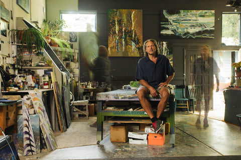Kevan Krasnoff sits on the work table at his studio in Boulder, CO