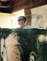 Ian Ratowsky holding up a large completed canvas painting of a horse