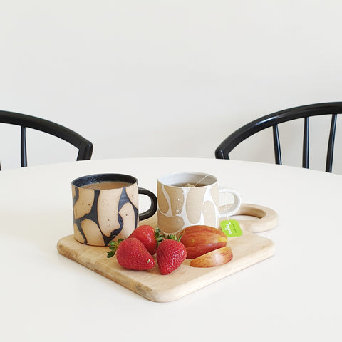 two hand made mugs sit on a tray with fruit