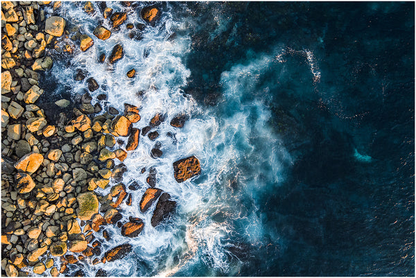 Aerial view of the early morning sunlight on the rocks at Cabbage Tree Bay