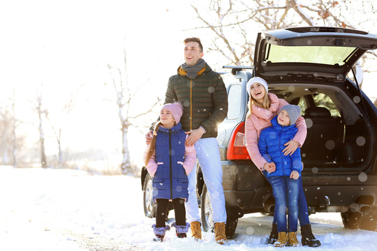 family with car in snow road trip travel organization