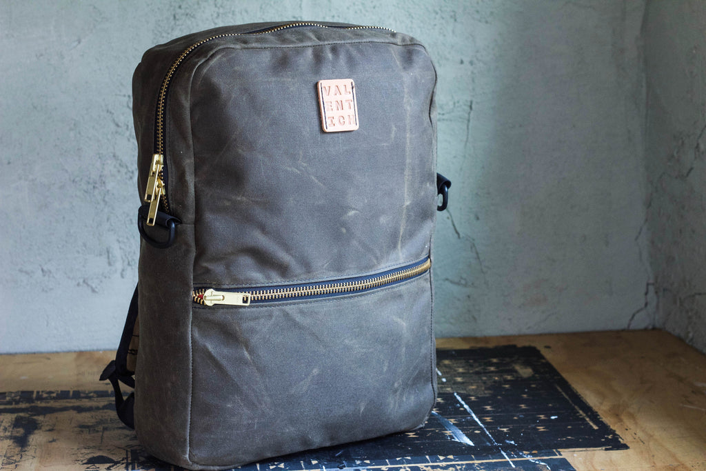 brown waxed canvas backpack w/ cross-body strap