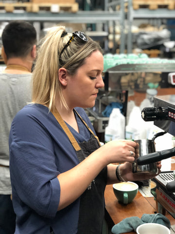 blonde girl making coffee at extract coffee in blue top