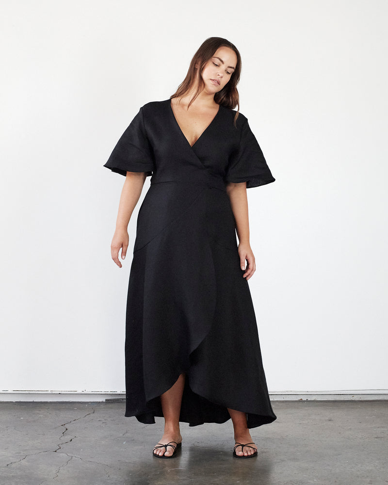 woman wearing black linen wrap dress