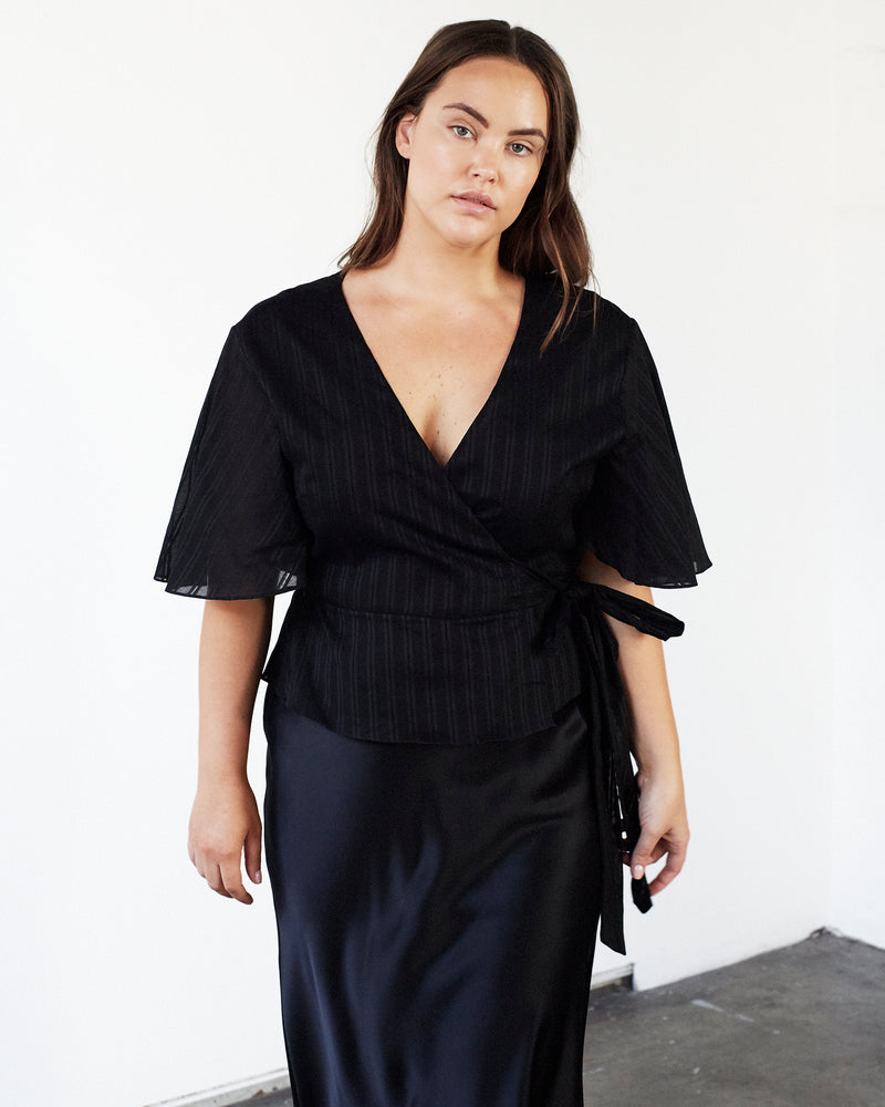 woman wearing black cotton wrap top with black silk skirt