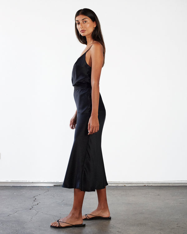 woman wearing black silk cami top and midi silk skirt