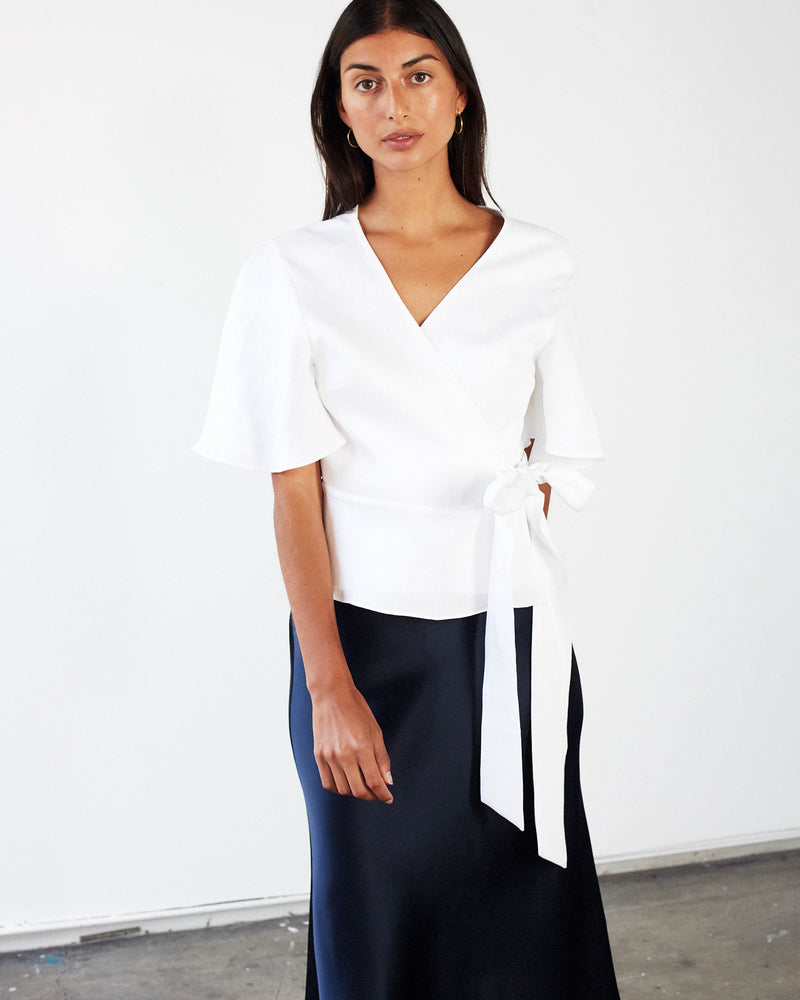 woman wearing white linen wrap top with black silk skirt