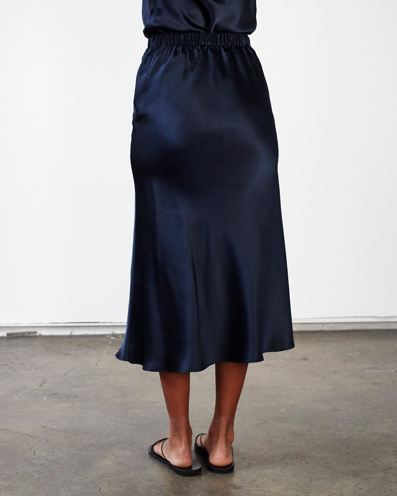 woman wearing navy silk cami top and midi silk skirt