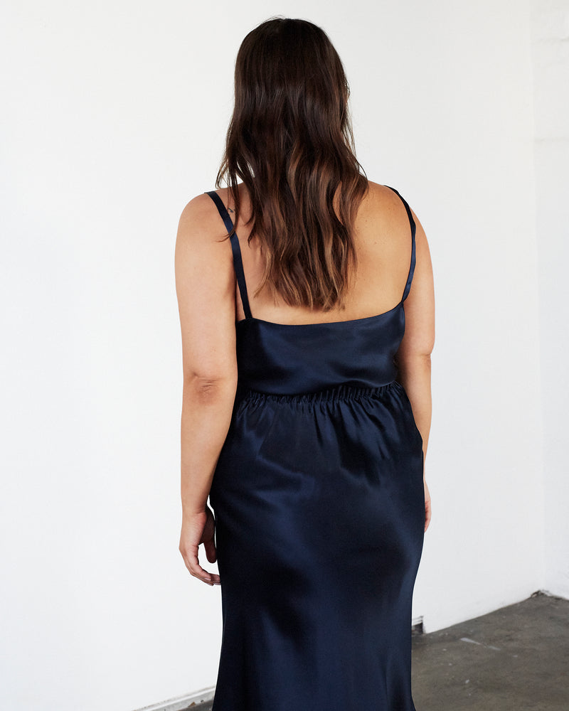 woman wearing round neck navy silk camisole and silk skirt