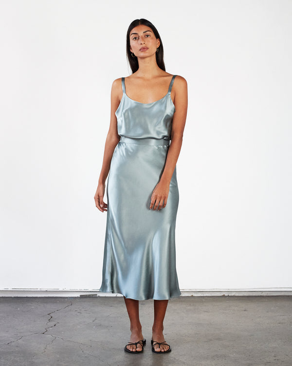 woman wearing round neck green silk camisole and silk skirt