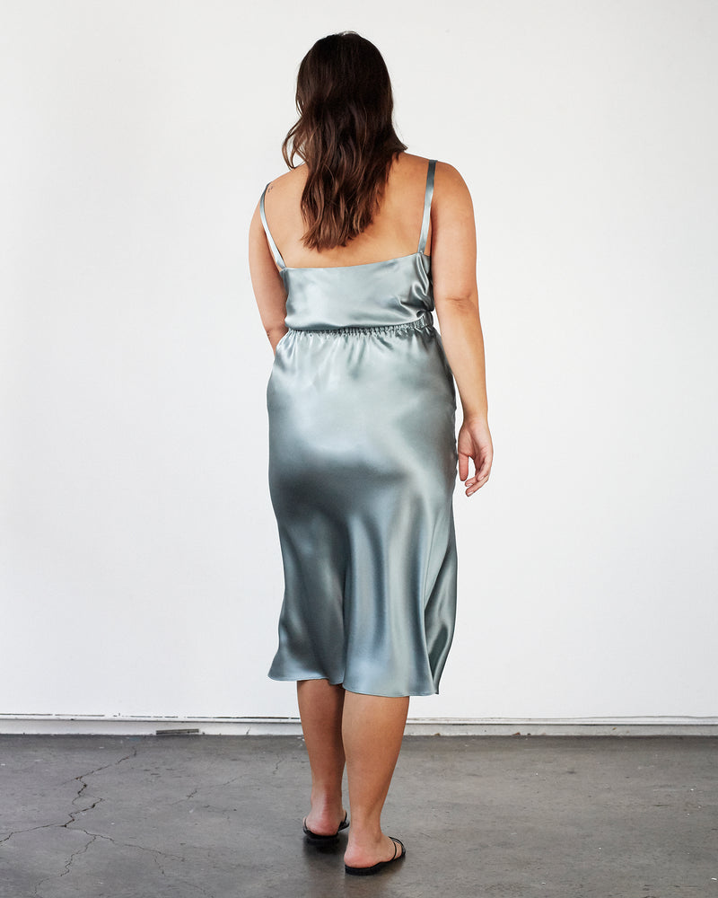 woman wearing green silk cami top and midi silk skirt