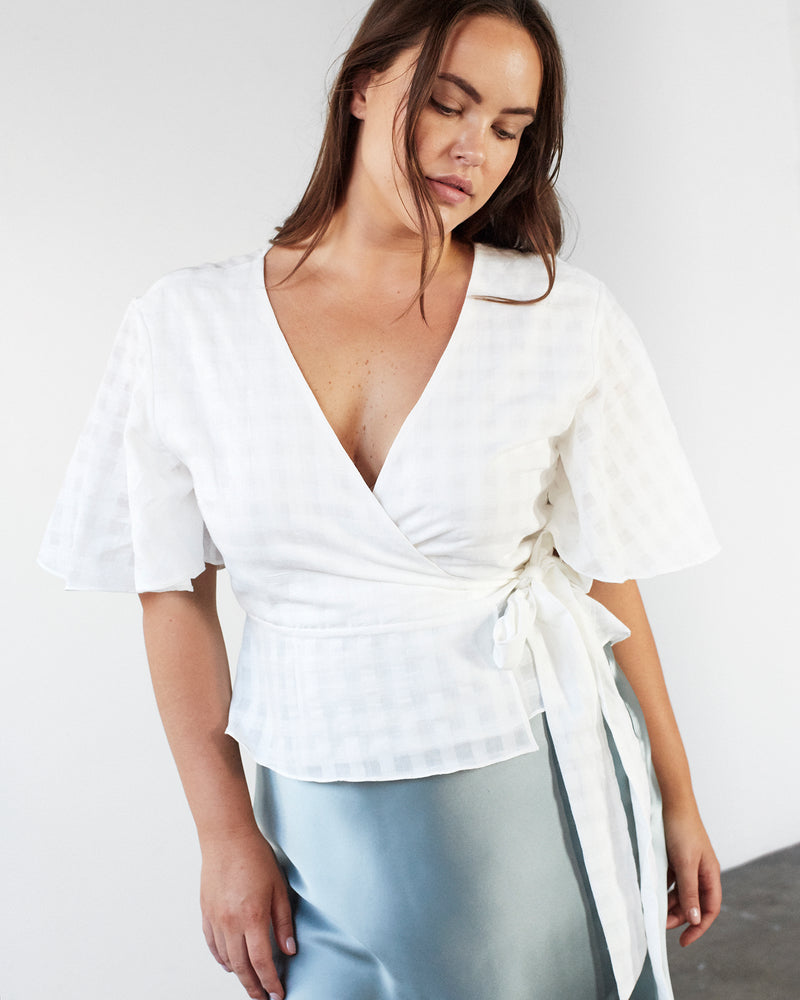 woman wearing white cotton wrap top with green skirt