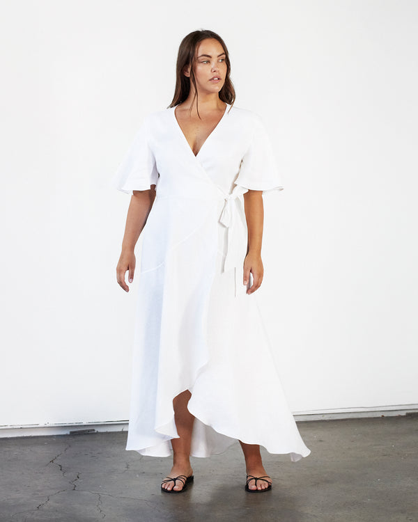 woman wearing white linen wrap dress