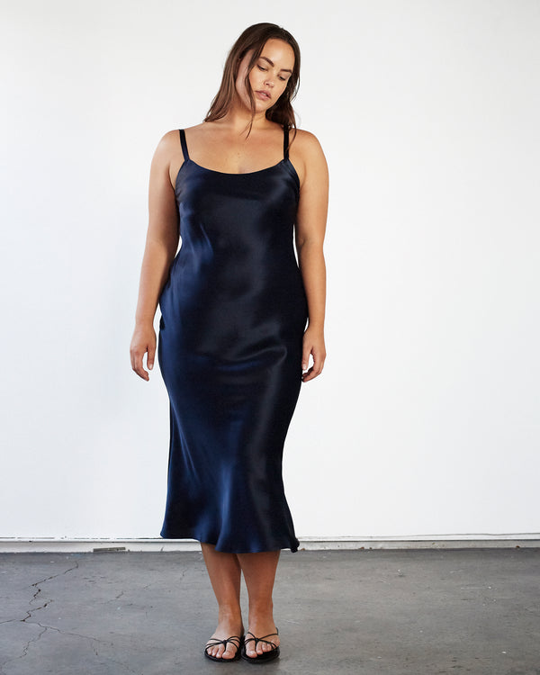 woman wearing round neck navy silk slip dress
