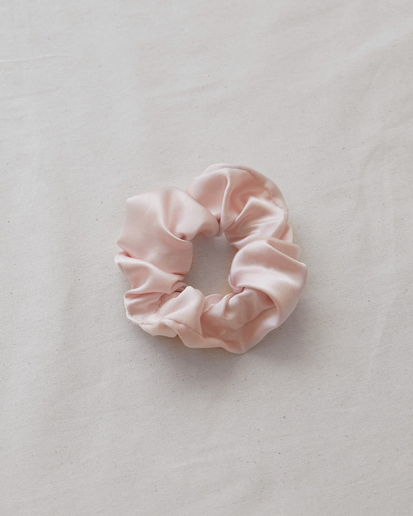 woman wearing pink silk scrunchie in hair