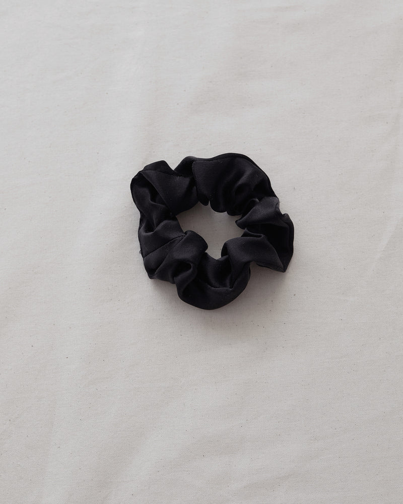 woman wearing black silk scrunchie in hair