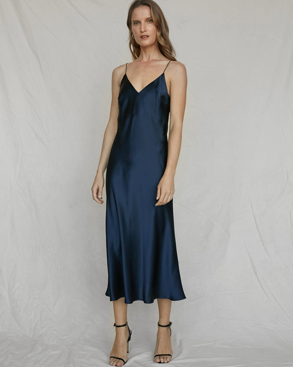 woman wearing navy v neck silk slip dress