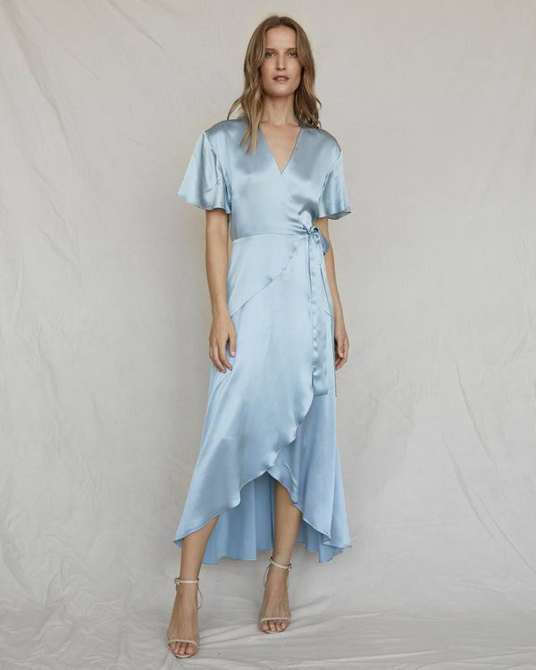 woman wearing light blue silk wrap dress