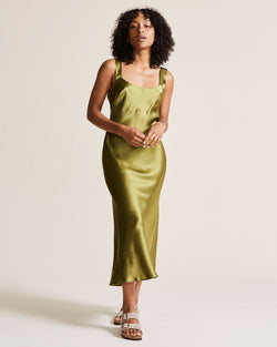 woman wearing green gold silk slip dress