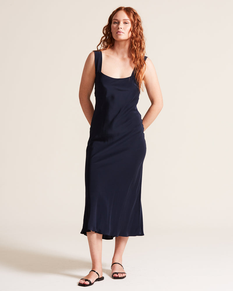 woman wearing long navy silk slip dress