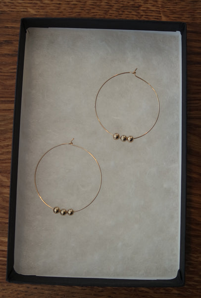 14k gold delicate beaded hoop finished with simple closure.