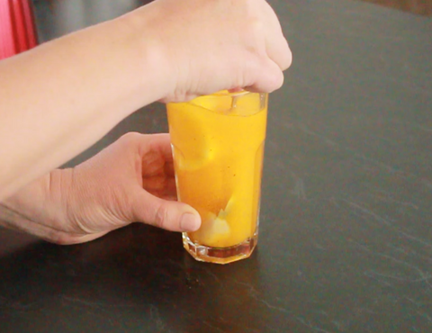 There are two hands cupping a clear glass which contains a warm elixir of K4 Cultured Turmeric Tea and lemon slices.