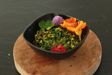 A bright herbed salad with golden vinaigrette is ensconced in a black bowl, garnished with flowers, microherbs and ruby sauerkraut.