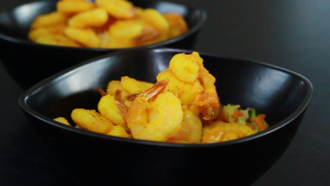 In a small, shiny bowl sits warm golden turmeric prawns on a bed of vegetable rice.