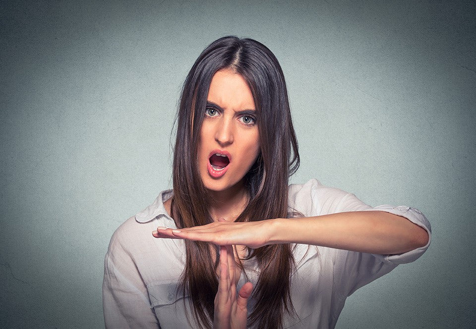 "A woman with long dark hair is looking directly at the camera with an intense and angry expression with her mouth partly open as if she is shouting, she is wearing a white shirt and had her two hands held up in the ""time-out"" symbol"