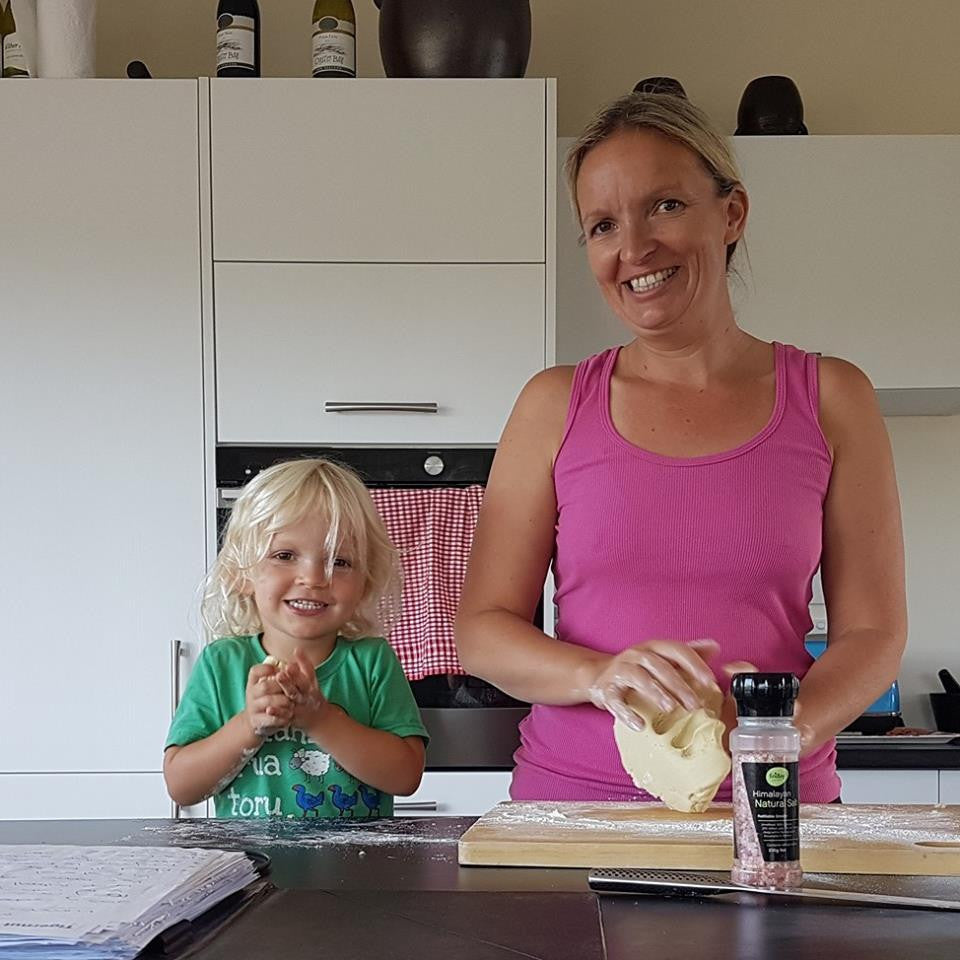 Mumma and 3 year old son standing in the kitchen, kneading a kumara and cassava flour dough to make tortillas, smiling happily at the camera