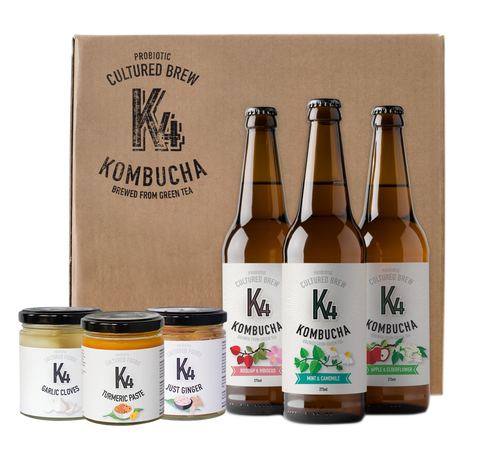 A cardboard case stamped with the K4 Brand Logo, with 3 bottles of K4 Kombucha and a jar each of K4 Cultured Turmeric Paste, K4 Cultured Garlic Cloves and K4 Cultured Just Ginger are arranged in trios in front of the case.