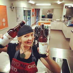 Woman standing in a commercial kitchen wearing a cap backwards and a red apron, she is smiling at the camera and holding up three swing top bottles of Kombucha.