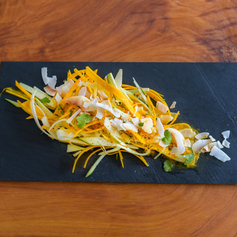 On a natural timber background sits black slate, topped with Fresh Vegetable 'Pasta' Ribbons with Coconut, Black Sesame & K4 Cultured Turmeric, garnished with toasted coconut and microherbs.