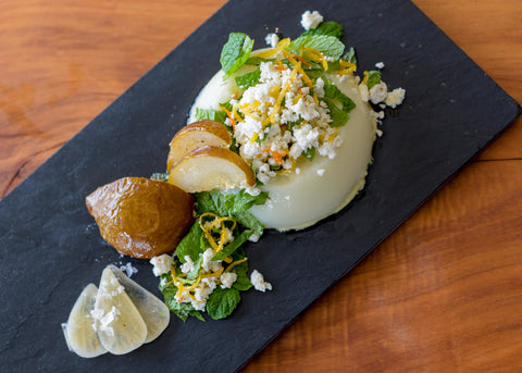 Garlic Pannacotta with Roasted Pear, Feta Crumb and Mint is decoratively placed on black slate with a natural timber background, fresh herbs and cultured garlic adorn the dish and it looks fit for a queen.