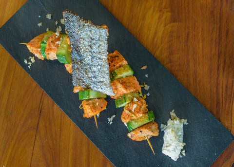Three K4 Cultured Ginger Skewered Salmon and Cucumber with citrus salt and crispy salmon skin on black slate, with a natural timber background.  It looks delicous...!