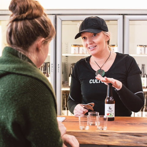 A customer at the K4 Brewery is talking to Kaye about K4 Kombucha over a bar, on the bar are three tasting glasses and a chilled bottle of Apple & Elderflower K4 Kombucha.  Kaye is standing behind the bar, and in front of a 3 door glass display chiller that is filled with chilled K4 Kombucha and K4 Cultured Foods.