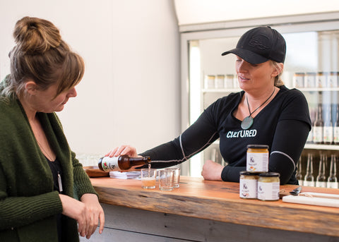 One woman standing at a bar being served K4 Kombucha by another woman, both are interested in the effervescent bubbles coming from the Kombucha as it is poured.