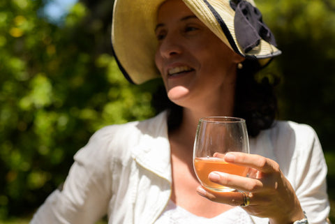 A woman with dark hair and a beautiful wide brim hat holds a glass of dusky pink Kombucha in her hands and smiles while looking beside and past the camera