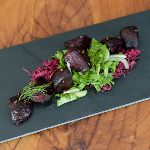 Roast Beetroot Salad with Fennel, Salted Bok Choy and Garlic Cream presented on a bed of ruby sauerkraut, displayed on black slate on a natural timber board. The dish is garnished with fresh fennel fronds, seeds and glossy olive oil, and looks delicous.