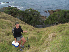 Woman wearing shorts and a beanie, holding a fishing rod and tackle box, standing on the top of a large hill on Urupukapuka Island, New Zealand
