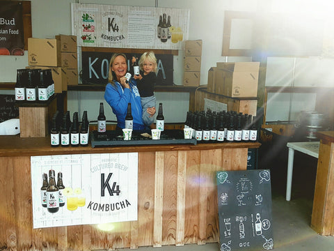 A photo taken at a farmers markets, there is a rustic wooden stall in the centre of the photo, the benchtops are covered in glass bottles of Kombucha and a woman and a 4 year old boy are standing in the stall, happily holding bottles up to the camera and smiling.